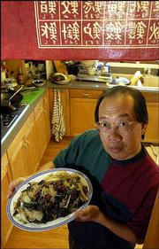 Pok Chi Lau, Lawrence, displays a vegetable stir fry he prepared in a wok. Lau, a Kansas University professor of photography, learned how to cook in a Chinese restaurant in Halifax, Nova Scotia.