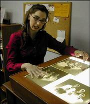 Rebecca Phipps continues to review, catalog and file 36,000 photographic prints and glass negatives such as these at the Carroll House Museum in Leavenworth. Phipps, the museum's curator for nearly two years, starts work next month as director of the Watkins Community Museum of History, 1047 Mass.