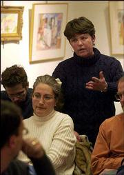Ann Goans, standing, discusses the importance of keeping small neighborhood schools open during a meeting of a group organizing to oppose the school bond issue. Goans aired her concerns Wednesday to attending school board candidates Cille King, Leonard Ortiz, Michael Pomes and Rich Minder's representative, Burdett Loomis. Seated at left is Deborah Snyder.