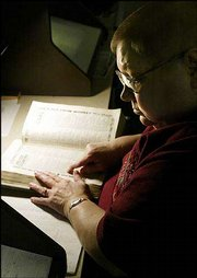 Carol McGee checks out an old directory for the name of an ancestor who died long ago. She is a volunteer at St. Louis Genealogy Society in Missouri.