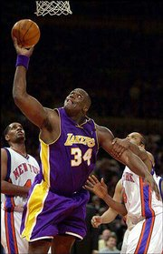 The Lakers' Shaquille O'Neal (34) is fouled by the Knicks' Latrell Sprewell, right, in the second half of the Lakers' 114-109 victory. O'Neal had 33 points in the win Thursday in New York.