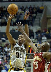 Indiana guard reggie miller shoots over Atlanta forward Glenn Robinson during overtime. Miller scored 26 points in the Pacers' 98-97 victory Friday at Indianapolis.