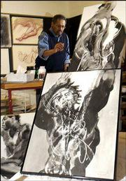 artist and KU architecture professor Hobart Jackson works on a figure study painting in his Lawrence studio. In the foreground are three examples of his ink drawings featuring black male models. Jackson is also a photographer who specializes in architectural photography.