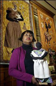 "artist marla jackson holds a doll titled ""Corporate Daycare,"" which was made by her mother, Fern Hale-Hopkins of Cleveland, Ohio. The dolls are on display this month along with Jackson&squot;s quilts at the Watkins Community Museum of History, 1047 Mass. Behind Jackson are two of her quilts ""Corporate Daycare,"" left, and ""Firstborn."""