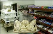 Sead Zulic, owner of the Golden Grain Bakery and Grocery, holds a display of Bosnian and European breads sold in his store. Zulic opened the first Bosnian business and bakery in the Bevo Mill section of St. Louis, which during the past 10 years has seen a large influx of Bosnians.