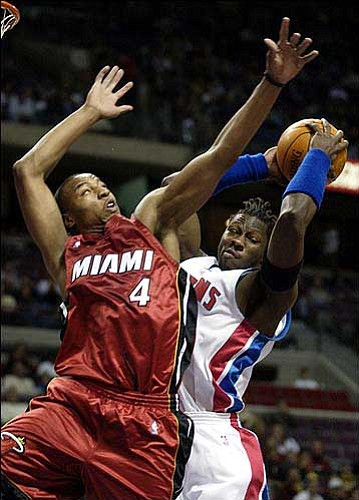 Detroit's Ben Wallace, right, grabs a first-quarter rebound from Miami's Caron Butler. The Pistons beat the Heat, 93-62, Monday in Auburn Hills, Mich.