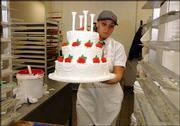 Ericka Morris finishes off a wedding cake for a customer at Hy-Vee Food Store. The cake has buttercreme icing and is highlighted with roses made of frosting. Lawrence cake decorators say customers seem to prefer cakes in which the layers are simply stacked, like the one pictured above, rather than tiered cakes where layers are separated by tall columns.