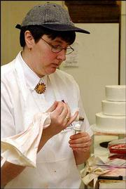 Helen Benefiel, a longtime Lawrence cake decorator, works on a flower for a wedding cake at Hy-Vee Food Store, 3504 Clinton Parkway. Benefiel, who won the International Dairy-Deli-Bakery Assn.'s Cake Decorating Challenge, says there is a move toward more unusual, fancy cake flavors and fillings.
