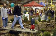 Heather and John Nichols and their son, Jackson, 3, Lawrence, walk over a garden pond created by AquaTerra Waterscaping and Stoney's Creative Landscaping & Design during the third annual Lawn, Garden and Home Show Saturday at the Douglas County 4-H Fairgrounds.