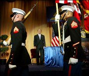 President Bush, center, watches as members of the Marine Color Guard leave the stage area before delivering remarks at the American Enterprise Institute annual dinner. Bush on Wednesday night laid out his postwar vision for the Arab world.