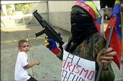 A boy is frightened by Mary Parra, who is dressed as a terrorist, for a protest march in Caracas, Venezuela. Opponents of President Hugo Chavez marched Wednesday through the streets of Caracas, forcing the postponement of talks between government and opposition delegates on ending the country's political and economic turmoil.