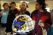 From left, Emily Torres, 14, Erica Demby, 11, Jamica Brouhard, 12, and Rachelle Moeding, 14, view a Jayhawk Tiffany-style lamp at the Boys & Girls Club of Lawrence, 1520 Haskell Ave. The Lawrence St. Patrick's Day Parade Committee announced Wednesday that proceeds from all the committee events this year will go to the Boys & Girls Club's after-school program.