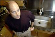 Noah Eckhouse stands by the sink and faucet fixture that he bought online for his Lincoln, Mass., home. Eckhouse, who has started several Internet sales companies himself, estimated that he would have paid 50 percent more had he purchased the two items from a traditional retailer. In California and many other states, lawmakers are trying to make it easier to tax Internet purchases.