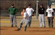 Free State high's Paul Metzler fields a grounder as Firebirds, from left, Jarid Moore, Matt Berner, Blake Dixon and Kyle Unruh look on. Monday was the first day spring sports were allowed to practice, and FSHS took advantage of the warm weather to practice outside.