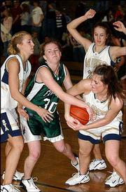 Free State senior Jayme Lisher (30) gets into a tug-of-war with Overland Park Aquinas defender Carolyn Sweeney, right, while Saints teammates Megan O'Malley, left, and Emily Mayfield converge. The Firebirds fell, 65-31, Friday at Aquinas.