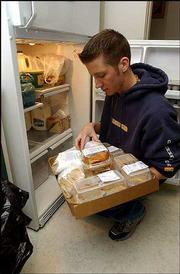 Jason Simon, a Kansas University sophomore from Andale, prepares meals at the Community Drop-In Center, 10th and Kentucky streets. Simon says he tries to help out at the center every Tuesday, but more volunteers are needed as the center deals with increased need and reduced funding.