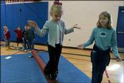 "Makayla Johnson, a kindergartner at Wakarusa Valley School, crosses a balance beam while sixth-grader Holly Harrison spots her during a physical education class. An exercise program at Wakarusa Valley called ""Get Moving"" motivates children to exercise."