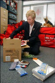 Barbara Wilson, an Armed Forces Emergency Service Volunteer at the American Red Cross, packs up items for a care package.