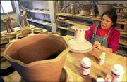 Artist Lynda Feman, shown here painting a cake stand at her New Mexico pottery studio, is in favor of a higher minimum wage for those working in Santa Fe, N.M. The proposal has led to a fight pitting some of Santa Fe's biggest employers against its poorest residents.