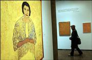 A visitor walks through the Beauford Delaney retrospective exhibit at the Carpenter Center for the Visual Arts on Harvard University's campus in Cambridge, Mass. A portrait of singer Marian Anderson, left, among 29 Delaney paintings on view at the center through May 4, demonstrates the artist's love for the color yellow.