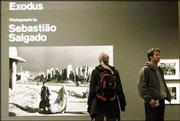 "Visitors look at some of Brazilian photographer Sebastiao Salgado&squot;s photographs in his exhibition at the Barbican Gallery in London. ""Exodus,""&squot; a collection of 350 black-and-white photographs, explores the phenomenon of mass migration at the end of the 20th century and is the first major showing of Salgado&squot;s work in Britain in 10 years."