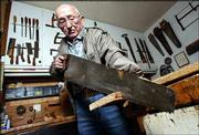 Arthur L. Yager, 86, uses an English saw, at least 100 years old, to cut a board in the workshop of his Fresno, Calif., home. Yager, a lifelong carpenter, has a collection of old and antique tools he uses for woodworking.