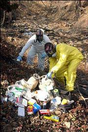 "Franklin County Sheriff&squot;s deputies demonstrate a cleanup of waste from a methamphetamine lab discarded in a rural area. Items dumped by a manufacturer of the illegal drug might include propane tanks, coffee filters, coolers, lithium batteries and aluminum foil. Jeff Curry, a deputy with the Franklin County Sheriff&squot;s Department, calls such an area ""the equivalent of a small toxic waste site."""