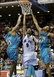 Orlando's Drew Gooden, center, shoots between New Orleans' Jamaal Magloire, left, and P.J. Brown for two of his nine points. Gooden grabbed 11 rebounds in the Magic's 96-86 victory Saturday night in Orlando, Fla.