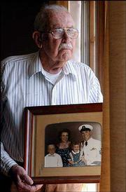 Donald Binns holds a picture of himself in uniform before going off to World War II. Binns, 85, was captured on Guam and spent most of the war as a prisoner of war. Also shown in the old photograph are his wife, Eunice, who passed away seven years ago, his son, Donald Victor, and daughter, Joanne Eunice.