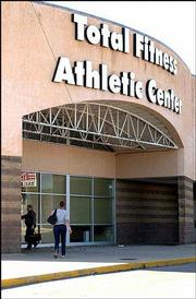 Total Fitness Athletic Center members enter the building at 2339 Iowa. Marty Tuley, owner/operator of the center, has sent a letter to club members saying that the center may close in the near future because of legal troubles.