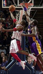 Houston guard Steve Francis, left, goes up against Lakers center Shaquille O'Neal for two points. The Lakers beat the Rockets, 96-93, Wednesday in Houston.
