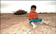 An Iraqi child sits on the ground as 2nd Royal Tank Regiment of the British Army passes by in the background. The tanks were moving Wednesday near Basra, Iraq.
