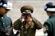 A North Korean soldier looks toward the South through a pair of binoculars, between two South Korean soldiers at the demilitarized zone in the border village of Panmunjom between the two Koreas. North Korea on Wednesday cut off the only regular military contact with the U.S.-led United Nations Command that monitors the Korean War armistice, accusing the United States of trying to attack the communist state.