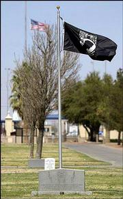 A U.S. flag flies at half-staff, rear, as a POW-MIA flag flies over a monument honoring past prisoners of war at the Fort Bliss U.S. National Cemetery in El Paso, Texas. A unit of the 507th Maintenance Company based at Fort Bliss is missing in Iraq.