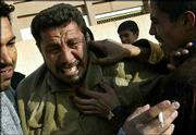 Ahmed weeps upon learning of his 22-year-old son's death at Al-Yarmouk hospital Thursday in Baghdad. Ali Ahmed was a Fedayeen fighter killed by coalition forces.