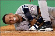 Yankees shortstop Derek Jeter grimaces after he collided with Toronto catcher Ken Huckaby at third base. New York beat the Blue Jays, 8-4, Tuesday in Toronto, but the Yankees' All-Star suffered a dislocated shoulder on the play.
