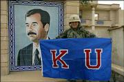 "U.S. Army Capt. Brad Loudon displays a Kansas University flag in front of a portrait of Iraqi President Saddam Hussein. Friends and family say Loudon, ""a big KU basketball fan,"" is in or near Baghdad with the 2nd Battalion, 70th Armored Regiment from Fort Riley."