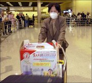 A passenger wearing a mask to protect herself from severe acute respiratory syndrome arrives at Los Angeles International Airport. She traveled Friday from Hong Kong, where the illness is more widespread. President Bush Friday approved the use of quarantines for Americans with the disease.