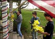 Jim Butler, left, and his sons Josh, center, and James Jr. put up yellow ribbons Thursday on the front porch of their Wellsville home. The Butler family is mourning the loss of their son and brother, Army Sgt. Jacob Butler, who was killed Tuesday in Iraq. The Butlers eventually added black ribbon to the yellow.
