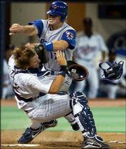 Toronto's Josh Phelps, right, collides with Minnesota catcher A.J. Pierzynski. Phelps was out at the plate, and the Blue Jays beat the Twins, 7-2, Friday in Minneapolis.