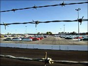 Barbed wire frames a lot full of General Motors electric cars at a GM testing and repair facility in Van Nuys, Calif. As California retreats from its strict pollution regulation, GM is taking the electric cars off the road when leases expire because it can no longer supply parts to repair them, GM spokesman Dave Barthmuss said.