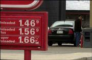 Lance Dirk, Lawrence, fills up at Presto, 1802 W. 23rd St. The Energy Department revised its gasoline price forecast on Tuesday, saying it expects prices to continue to drop. It is forecasting a national average price of $1.56 a gallon this summer.