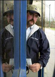 Attendant Tony Klamm is reflected in the glass of his tollbooth as he hands tickets to drivers at the east Lawrence entrance to the Kansas Turnpike. Officials say toll collectors will not lose their jobs when ticket-issuing machines are installed at many turnpike toll plazas.