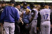 Kansas City players surround security guards as a fan is removed from the field after attacking first-base umpire Laz Diaz in the ninth inning. Tuesday's game was the first the Royals have played in Chicago since two fans attacked first-base coach Tom Gamboa last September. Tuesday's game was plagued with fans who ran onto the field at U.S. Cellular Field.