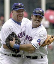 Texas' Kevin Mench, left, and Rafael Palmeiro celebrate a win against Anaheim. The Rangers defeated the Angels, 9-7, Thursday in Arlington, Texas.