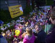 Mourners gather at Laci Peterson's home in Modesto, Calif. Police confirmed Friday evening that two bodies found near the San Francisco Bay several days ago were those of Peterson and her infant son.