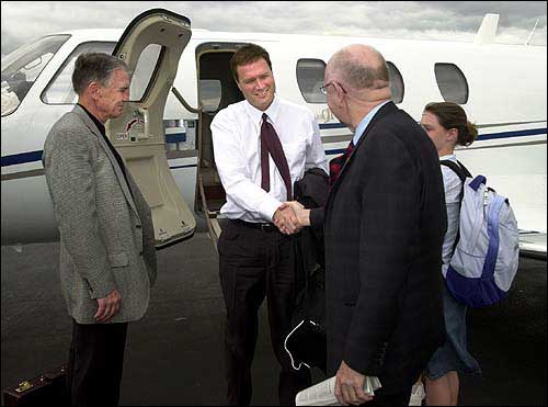 Kansas University interim athletic director Drue Jennings, left, looks on as KU Chancellor Robert Hemenway, second from right, greets Illinois basketball coach Bill Self, center, who arrived with his family, including daughter Lauren, right, at Lawrence Municipal Airport. Though Hemenway and Jennings declined comment on