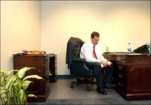 Greeted by an empty desk and blank walls, Bill Self opens a piece of mail in his new office. Self, who was hired as Kansas University's new men's basketball coach, moved Monday into Roy Williams' old office.