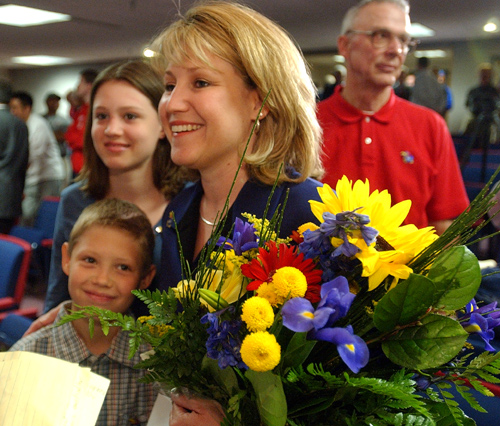 The Self family, clockwise from upper left, Lauren, 12, Cindy (holding flowers) and Tyler, 9, greet passersby after a news conference in which Bill Self was appointed the new KU men's basketball coach.