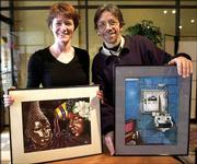 "Findlay High School art teacher Valerie Devitt, left, and artist Philip Sugden hold art works by Lima Correctional Institution inmates, on display at a Findlay, Ohio, coffee house. The works are Charles Hester's ""Ladies Day,"" left, and Willie Hightower's ""A 10,950 Day View."""